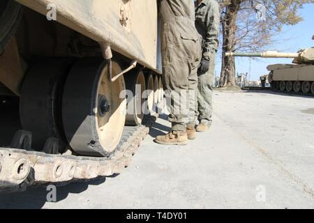 Two U.S. Army Tank Crew Members assigned to Charlie Company, 1st Battalion, 16th Infantry Regiment, 1st Armored Brigade Combat Team, 1st Infantry Division begin preventative maintenance checks and services on their assigned M1 Abrams tank during command maintenance, March 25, 2019. The unit is deployed to Romania in support of the Atlantic Resolve Mission. - Stock Photo