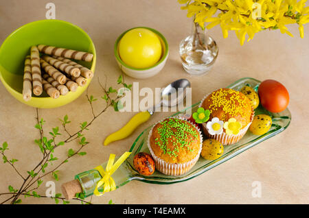 Muffins decorated with sprinkles, flowers of mastic, colored easter quail eggs on a kitchen table. Top view. Happy Easter holiday and greeting card co - Stock Photo