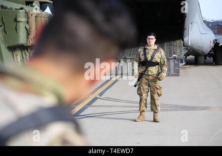 """Private Dominic Gonzalez, an Infantryman with """"Attack"""" Company, 3rd Battalion, 161st Infantry Regiment prepares to ground guide a Stryker Fighting Vehicle in to a C-17 operated by the 62nd Airlift Wing at Grays Army Airfield, Joint Base Lewis-McChord on April 4, 2019. The equipment load up is part of a week-long training exercise for the battalion that starts at unit home stations, flying to Moses Lake Airport, then convoying to Yakima Training Center. - Stock Photo"""