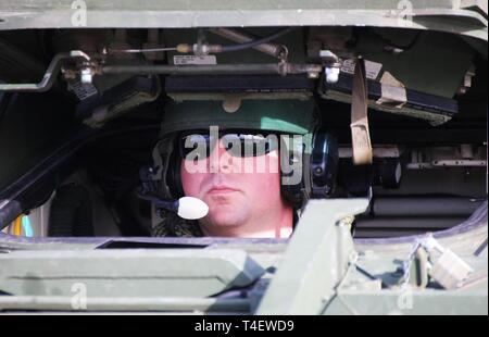 """Spc. Justin Holland, Infantryman with """"Attack"""" Company, 3rd Battalion, 161st Infantry Regiment prepares to drive his Stryker Fighting Vehicle in to a C-17 operated by the 62nd Airlift Wing at Grays Army Airfield, Joint Base Lewis-McChord on April 4, 2019. The equipment load up is part of a week-long training exercise for the battalion that starts at unit home stations, flying to Moses Lake Airport, then convoying to Yakima Training Center. - Stock Photo"""