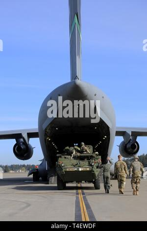 """A Stryker from """"Attack"""" Company, 3rd Battalion, 161st Infantry Regiment being loaded in to a C-17 operated by the 62nd Airlift Wing at Grays Army Airfield, Joint Base Lewis-McChord on April 4, 2019. The equipment load up is part of a week-long training exercise for the battalion that starts at unit home stations, flying to Moses Lake Airport, then convoying to Yakima Training Center. - Stock Photo"""