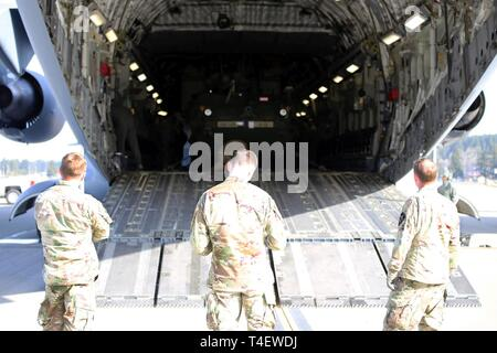 From left to right: 3rd Battalion, 161st Infantry Regiment leadership, Command Sgt. Major Carter Richardson, Capt. Jeremy Catob and Lt. Col. Matthew James observe their Strykers being loaded in to a C-17 operated by the 62nd Airlift Wing at Grays Army Airfield, Joint Base Lewis-McChord on April 4, 2019. The equipment load up is part of a week-long training exercise for the battalion that starts at unit home stations, flying to Moses Lake Airport, then convoying to Yakima Training Center. - Stock Photo