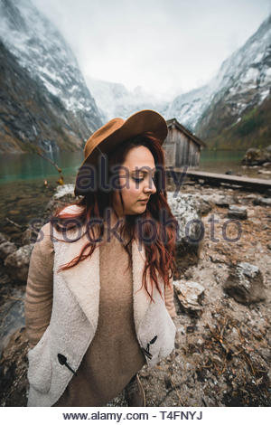 photography of woman standing beside brown stone between mountain during daytime - Stock Photo