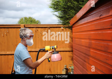 Middle-aged woman spray painting her fence, wearing the correct protective gear. - Stock Photo