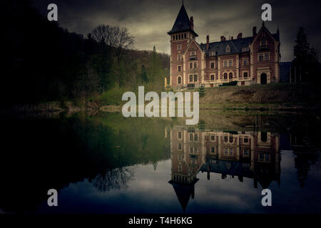 Scary view of a castle with a lake and reflection in the creepy forest - Stock Photo