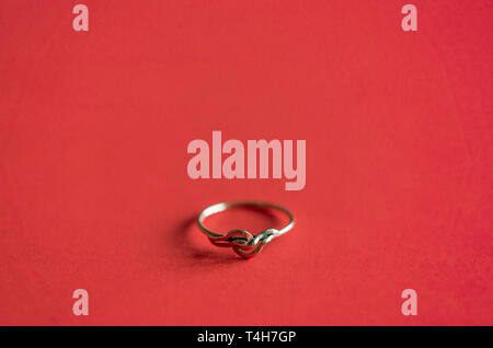 Close up / macro of a gold ring on coral red coloured background - Stock Photo