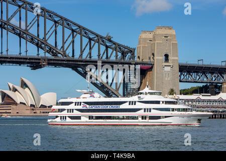 Captain Cook cruises boat vessel on Sydney harbour passing by the Sydney Opera House and Sydney Harbour bridge,Sydney,Australia - Stock Photo