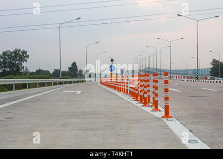 The orange traffic pole or flexible traffic bollard on asphalt road for crossroad - Stock Photo