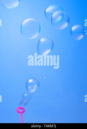 blowing soup bubbles on blue background - Stock Photo