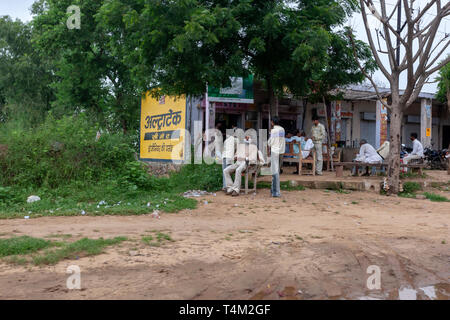 Man in a open rudimentary barber shop in a rural village in Rajasthan, India - Stock Photo