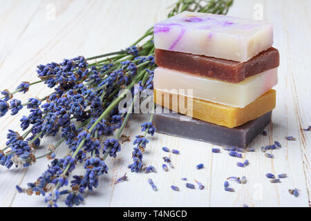 Natural handmade soap stack with lavender on wooden table - Stock Photo