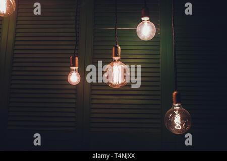 Decorative antique edison style light bulbs against brick wall background. - Stock Photo