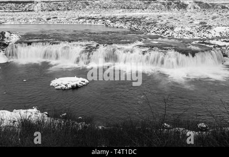 A black and white image taken in Winter of Faxi waterfall in Iceland, this is a stop on the Golden Circle Tour long exposure to smooth out the water - Stock Photo