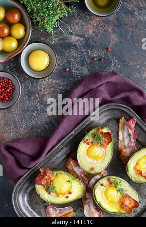 Baked avocado with egg and bacon on a metal baking tray, flat lay with ingredients and herbs on dark background - Stock Photo