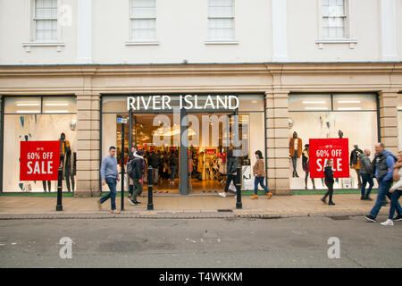 Shoppers walking past the high street  fashion clothes  shop retailer River Island in the town of Cheltenham Gloucestershire England UK - Stock Photo