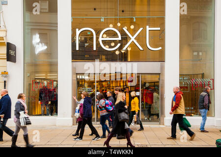 Shoppers walking past the high street  fashion clothes  shop retailer Next in the town of Cheltenham Gloucestershire England UK - Stock Photo
