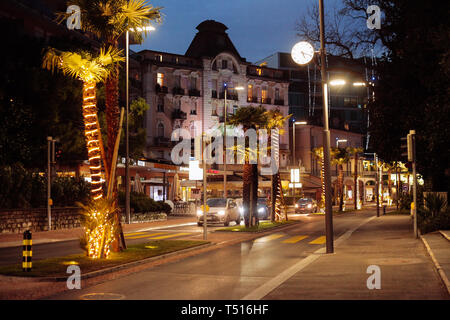 The city of Lugano in Switzerland during the holidays and Christmas is lit by bright lanterns. Streets of a festive night city - Stock Photo