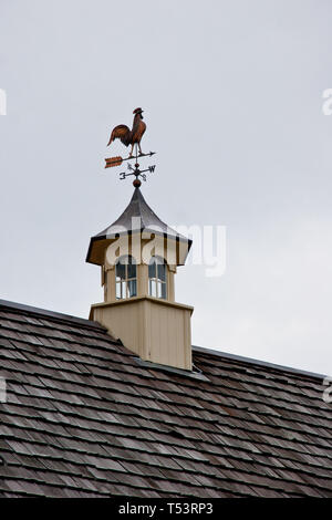 Cupola on top of a barn rook with a copper rooster weather vane - Stock Photo