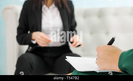 psychotherapeutic session. blurred businesswoman talks with his psychologist taking notes - Stock Photo