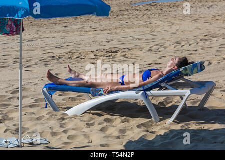 Bournemouth, Dorset, UK. 21st Apr 2019. UK weather: the heatwave continues with hot and sunny weather, as beachgoers head to the seaside to enjoy the heat and sunshine at Bournemouth beaches for the Easter holidays - mid morning and already beaches are getting packed, as sunseekers get there early to get their space. Woman in blue bikini sunbathing on sunlounger. Credit: Carolyn Jenkins/Alamy Live News - Stock Photo