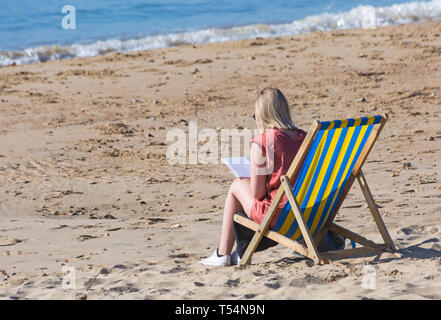 Bournemouth, Dorset, UK. 21st Apr 2019. UK weather: the heatwave continues with hot and sunny weather, as beachgoers head to the seaside to enjoy the heat and sunshine at Bournemouth beaches for the Easter holidays - mid morning and already beaches are getting packed, as sunseekers get there early to get their space. Woman sitting in deckchair reading book. Credit: Carolyn Jenkins/Alamy Live News - Stock Photo