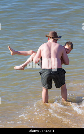 Bournemouth, Dorset, UK. 21st Apr 2019. UK weather: the heatwave continues with hot and sunny weather, as beachgoers head to the seaside to enjoy the heat and sunshine at Bournemouth beaches for the Easter holidays - mid morning and already beaches are getting packed, as sunseekers get there early to get their space. Man and boy having fun in the sea. Credit: Carolyn Jenkins/Alamy Live News - Stock Photo