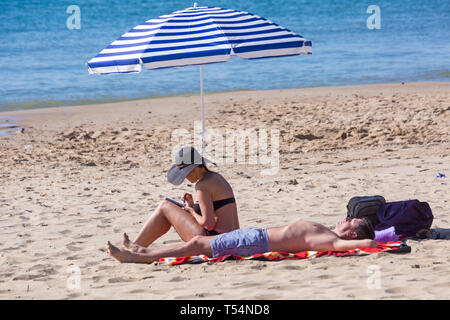Bournemouth, Dorset, UK. 21st Apr 2019. UK weather: the heatwave continues with hot and sunny weather, as beachgoers head to the seaside to enjoy the heat and sunshine at Bournemouth beaches for the Easter holidays - mid morning and already beaches are getting packed, as sunseekers get there early to get their space. Couple sunbathing under parasol. Credit: Carolyn Jenkins/Alamy Live News - Stock Photo