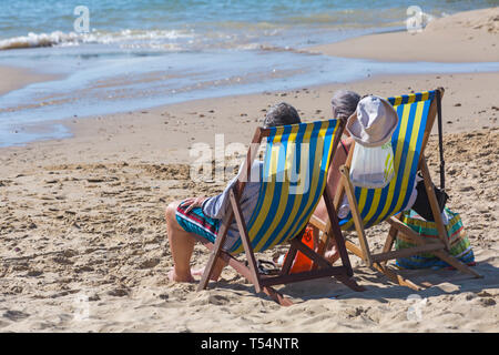 Bournemouth, Dorset, UK. 21st Apr 2019. UK weather: the heatwave continues with hot and sunny weather, as beachgoers head to the seaside to enjoy the heat and sunshine at Bournemouth beaches for the Easter holidays - mid morning and already beaches are getting packed, as sunseekers get there early to get their space. Couple in deckchairs - back rear view. Credit: Carolyn Jenkins/Alamy Live News - Stock Photo