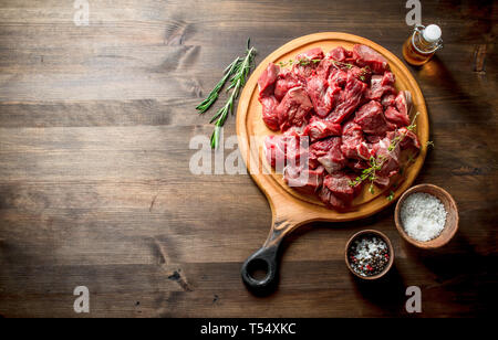 Cut raw beef with thyme,rosemary and butter. On wooden background - Stock Photo