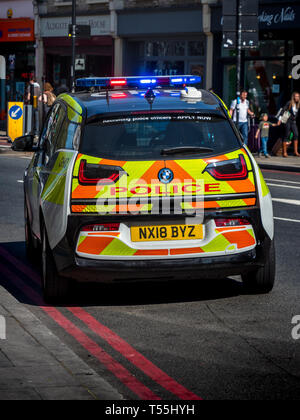 Electric Police Car with blue lights flashing on a call in London - London Metropolitan Police Electric Police Car BMW i3 - Stock Photo