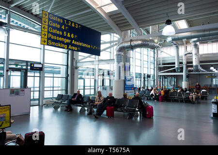 Passengers waiting in Bournemouth Airport departure hall interior with signs to gates - Stock Photo