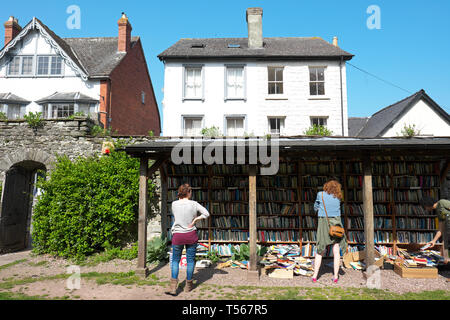 Hay on Wye Powys Wales - visitors browse the secondhand books for sale at the outdoor castle honesty bookshop in April 2019 - Stock Photo