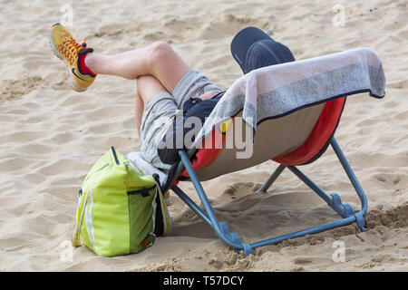 Bournemouth, Dorset, UK. 22nd Apr, 2019. UK weather: after a hazy start the glorious weather continues with hot and sunny weather, as beachgoers head to the seaside to enjoy the heat and sunshine at Bournemouth beaches on Easter Monday before the weather changes and the return to work. Man relaxing in chair on beach. Credit: Carolyn Jenkins/Alamy Live News - Stock Photo
