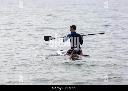 Bournemouth, Dorset, UK. 22nd Apr 2019. UK weather: after a hazy start the glorious weather continues with hot and sunny weather, as beachgoers head to the seaside to enjoy the heat and sunshine at Bournemouth beaches on Easter Monday before the weather changes and the return to work.  Paddleboarder paddle boarder. Credit: Carolyn Jenkins/Alamy Live News - Stock Photo
