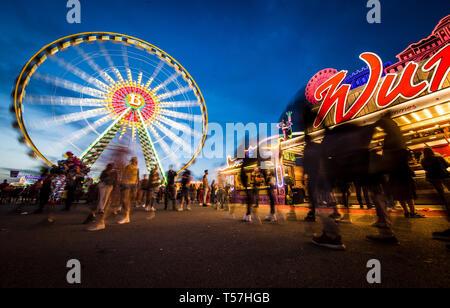 Stuttgart, Germany. 22nd Apr, 2019. Visitors enjoy the 81st Stuttgart Spring Festival at the Cannstatter Wasen at the blue hour. Credit: Christoph Schmidt/dpa/Alamy Live News - Stock Photo