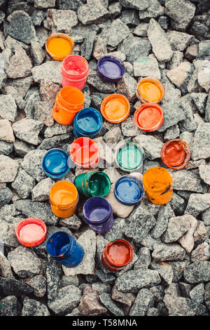 jar from under the paint of different colors on the rocks, view from above - Stock Photo