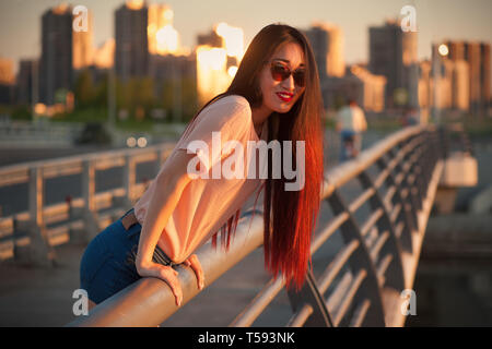 Asian girl in sunglasses leaning on the railing outdoors - Stock Photo
