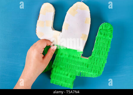Diy cinco de mayo Mexican Pinata Cactus made cardboard and crepe paper your own hands on a blue background. Gift idea, decor, game cinco de mayo. Step - Stock Photo