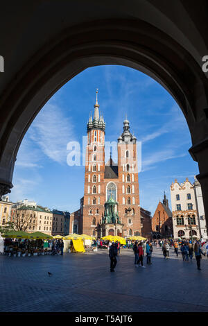Basilica of Saint Mary framed by an arch of the Cloth Hall arcade in Krakow, Poland, Gothic church at main square in the Old Town - Stock Photo