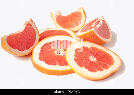 Sliced red grapefruit isolated on white background cut into several pieces and rings close-up. - Stock Photo
