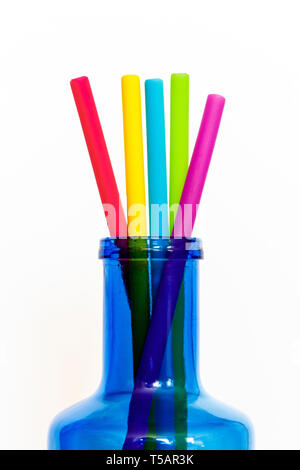 Close-up of brightly-coloured rubber reusable drinking straws projecting from the neck of a blue glass bottle, isolated against a white background - Stock Photo