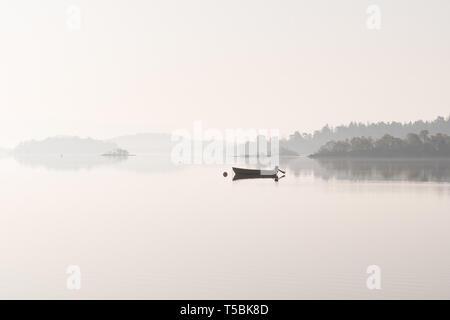 fishing boat on Loch Lomond near Luss in morning mist, Scotland, UK - Stock Photo