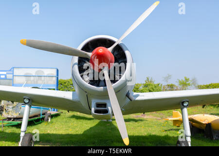 Cropped colour photograph of the front end of a classic training prop plane (P56 Provost) parked on grass in Dorset. - Stock Photo