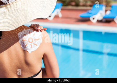 Gorgeous woman has a sun shaped sunblock on her shoulder by the pool. Sun Protection Factor in vacation, concept. - Stock Photo