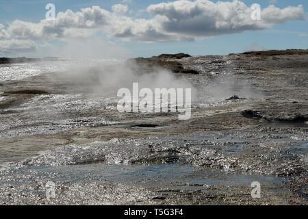 Seltun / Krysuvik (Krýsuvík): Fumarole emit sulphur gas behind geothermal field with puddles of hot water - Stock Photo