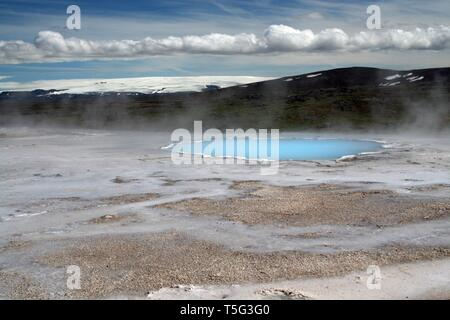 Seltun / Krysuvik (Krýsuvík): Steaming geothermal valley with natural blue pool and snowcapped mountain - Stock Photo