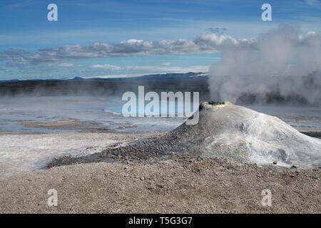 Seltun / Krysuvik (Krýsuvík): Mini volcano like fumarole emit sulphuric gas with steaming hot blue natural pool on geothermal field - Stock Photo