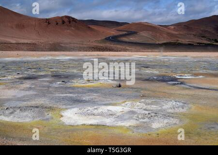 Seltun / Krysuvik (Krýsuvík): Road through red hills leading to yellow and white geothermal valley - Stock Photo