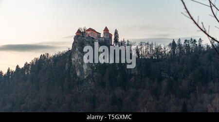 Medieval castle on Bled lake in Slovenia in the evening - winter - Stock Photo