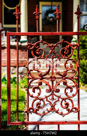 Reddish colored intricate wrought iron gate & fence - Stock Photo